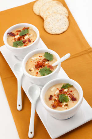 cooled: Three bowls of Chilled Corn and Bacon soup garnished with cooked bacon, fresh cilantro, and smoked paprika