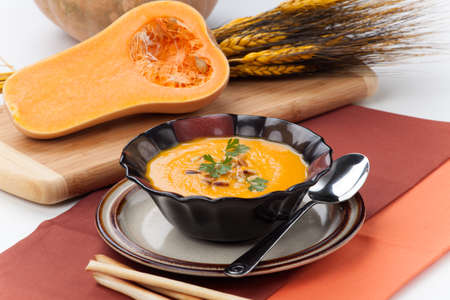 Hot delicious pumpkin soup in a bowl  Made from butternut squash  Garnished with roasted pine nuts, and fresh parsley  Banque d'images