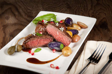 fingerling: Pan seared steak with fingerling potatoes, capers, pomegranate balsamic vinegar sauce, and fresh basil  Stock Photo