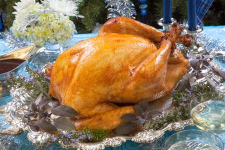 tacchino: Tacchino arrosto guarnito con erbe sul blu decorazioni di Natale, champagne e albero di Natale come sfondo