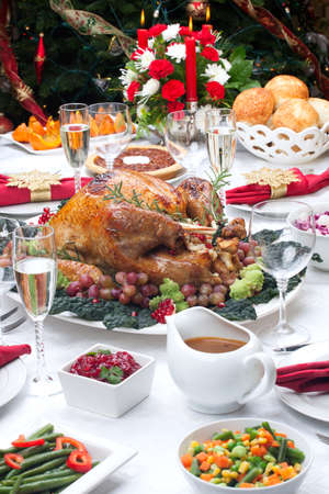 Holiday-decorated table, Christmas tree, champagne, and roasted turkey  photo