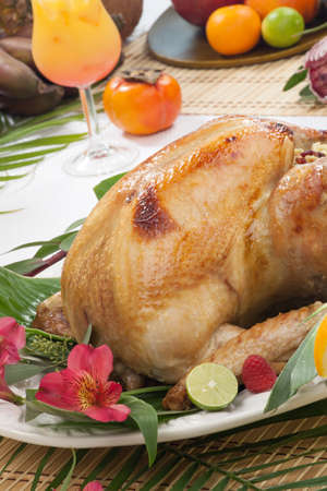 Garnished roasted turkey with tropical fruits, flowers, and refreshing cocktails for Thanksgiving  photo