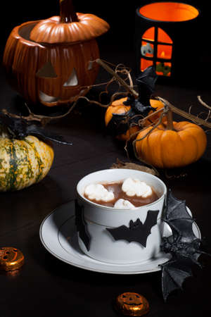 non: Cup of hot chocolate with ghost marshmallow, surrounded with pumpkins, candles, and Halloween decoration  Halloween drinks series  Stock Photo