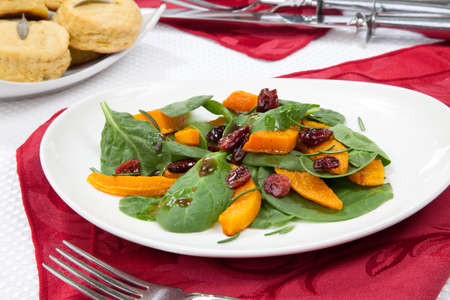 side salad: Roasted pumpkin and spinach salad, sage biscuits, and carved roasted spiced ham appetizers with Christmas ornaments  Stock Photo