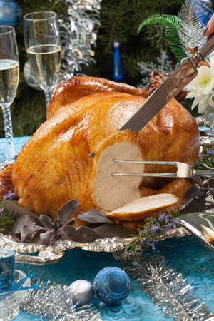 Carving roasted turkey garnished with herbs on blue Christmas decorations, and champagne  Christmas tree as background  Stock Photo