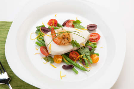 Poached halibut with spicy shrimp, green beans, cherry tomatoes, black olives, and citrus sauce  Stock Photo