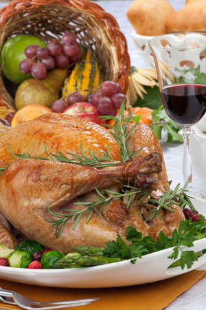plenty: Garnished roasted turkey on fall festival decorated table with horn of plenty and red wine Stock Photo