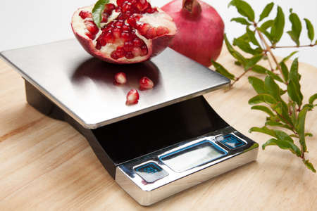 Digital kitchen scale on table and pomegranate