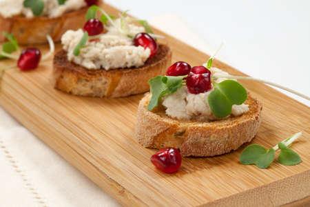 canapes: Wooden tray with three savory tuna salad crostini on white  Stock Photo