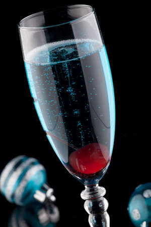chilled: Closeup of flutes of blue champagne cocktail, and Christmas ornaments on black background