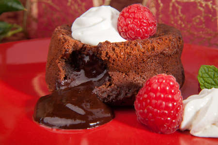Delicious dark chocolate lava cake dessert served with whipped cream and fresh raspberries  Surrounded by Christmas ornaments  Standard-Bild
