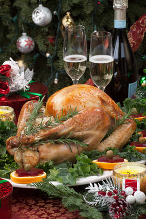 feast: Christmas-decorated table with feast, gifts, roasted turkey, candles, champagne, and Christmas tree on back