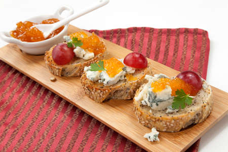 Blue cheese and apricot jam multigrain crostini with grapes and parsley on wooden tray  Apricote jam mini bowl