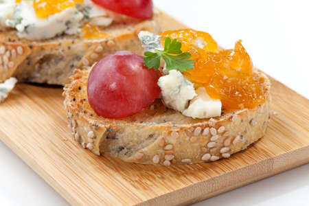 apricot jam: Blue cheese and apricot jam multigrain crostini with grapes and parsley on wooden tray  Apricote jam mini bowl