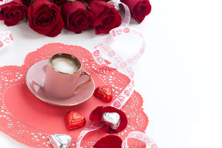 Closeup of cup of fresh coffee with red roses on Valentines day  photo