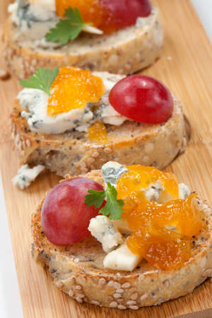 jam sandwich: Blue cheese and apricot jam multigrain crostini with grapes and parsley on wooden tray  Apricote jam mini bowl