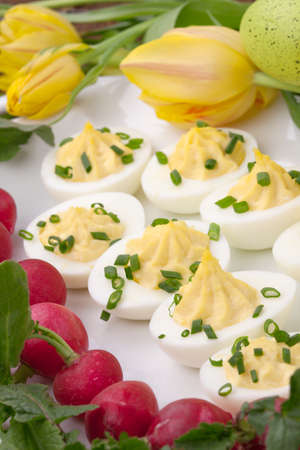 boiled eggs: Plate of deviled eggs, fresh radish, Easter decoration eggs, and fresh spring blooming tulips