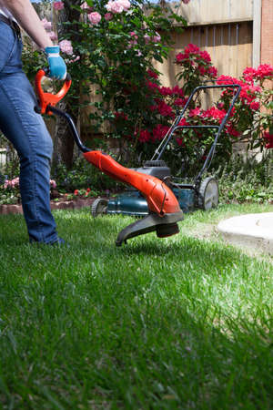 frontyard: Woman trimming lawn with electric edge trimmer