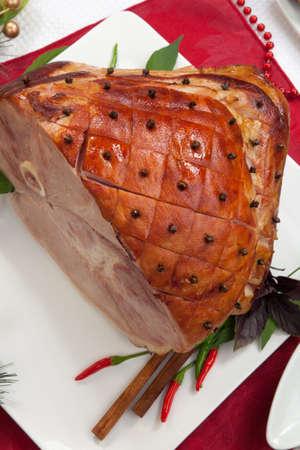 contorni: Prosciutto arrosto speziato sulla tabella di festa da pranzo, guarnita con chiodi di garofano, cannella, peperoncino, e viola Contorni basilico e addobbi natalizi in giro per Archivio Fotografico