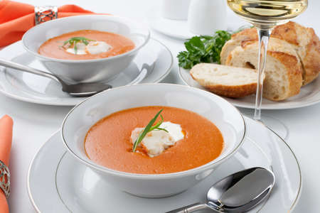 Two bowls of lobster bisque garnished with slice of lobster tail, cream, and fresh tarragon  Fresh backed Italian bread and white wine