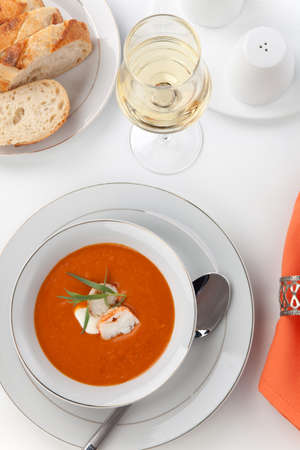 lobster tail: Two bowls of lobster bisque garnished with slice of lobster tail, cream, and fresh tarragon  Fresh backed Italian bread and white wine