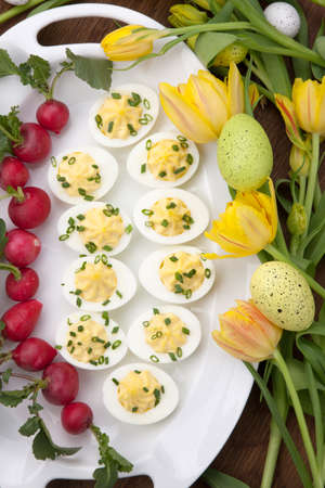 Plate of deviled eggs, fresh radish, Easter decoration eggs, and fresh spring blooming tulips  photo