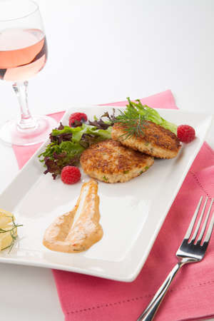 Two crab cakes appetizer garnished with spicy sauce, green salad, and raspbery