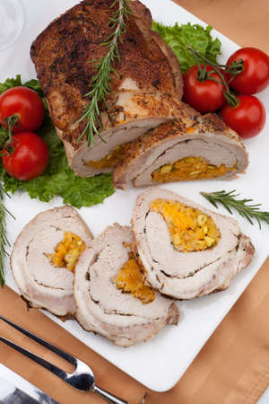 roulade: Dried apricots, pistachios, and rosemary staffed pork loin roulade served with salad, tomatoes and glass of red wine  Stock Photo