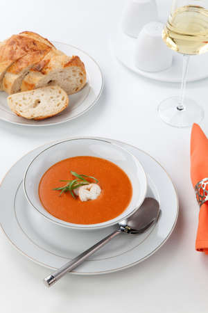 lobster tail: Bowl of lobster bisque garnished with slice of lobster tail, cream, and fresh tarragon  Fresh backed Italian bread and white wine  Stock Photo