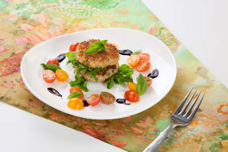 Close up of crab cakes and cherry tomato salad appetizer garnished with basil, and balsamic vinegar sauce  Stock Photo