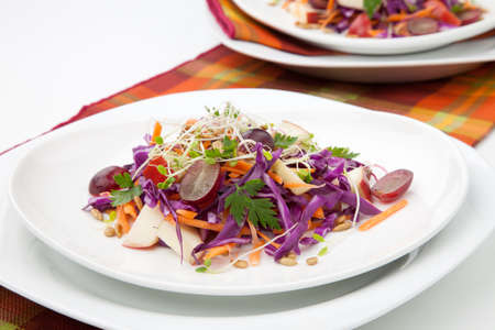 Closeup of red cabbage, carrot, and apple salad with sprouts, red grape, and roasted sunflower seeds served for healthy lunch Stok Fotoğraf