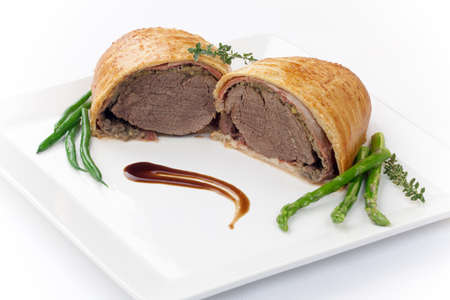 Beef Wellington - delicious roasted beef tenderloin rolled in mushroom puree and prosciutto, then wrapped in puff pastry  Garnished with green beans, tomatoes, and asparagus