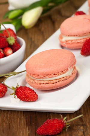 Closeup of a row of french strawberry macaroons with fresh alpine strawberries  photo