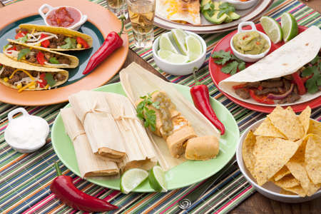 close up food: Assorted Mexican dishes, with chicken tamales with green salsa as the main subject  Stock Photo