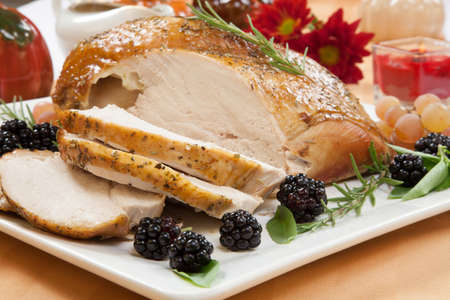 Carved Rosemary-basil rub roasted turkey breast garnished with grapes, blackberies, and fresh basil, and rosemary in fall themed surrounding  Stockfoto