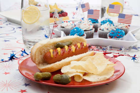 Hot dog, chips, and pickled cucumbers  Angel food fruit cakes and muffins on 4th of July in patriotic theme in background  photo