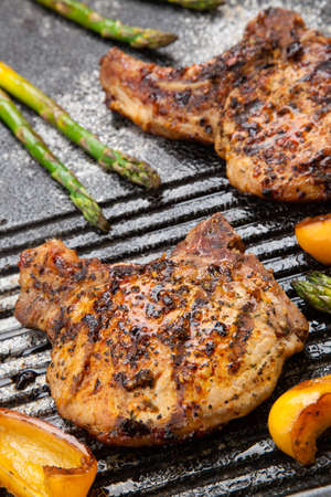 Juicy pork chops are grilled on griddle with asparagus and bell pepper  Backyard grilling for summer picnic