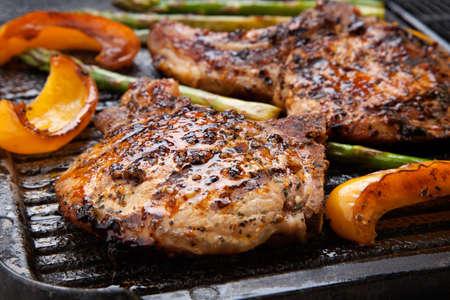 Juicy karbonades worden gegrild op bakplaat met asperges en paprika Backyard grillen voor de zomer picknick Stockfoto