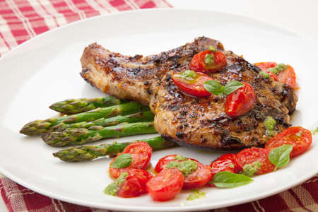 Grilled pork chops and asparagus  Served with fried grape tomatoes salad and pesto sauce
