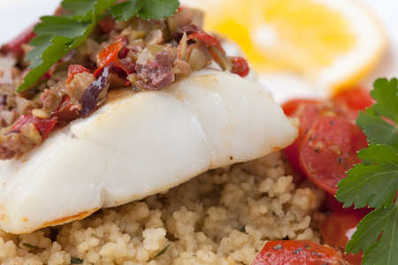 couscous: Baked halibut with olive tapenade crust garnished with couscous, fried cherry tomatoes, and fresh parsley  Stock Photo