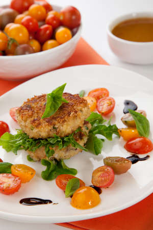 Close up of crab cakes and cherry tomato salad appetizer garnished with basil, and balsamic vinegar sauce  photo