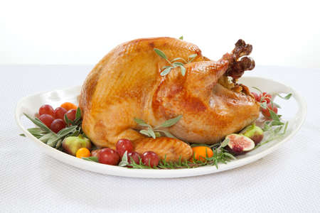 thanksgiving food: Roasted turkey on tray garnished with red grapes, figs, kumquat, and herbs over white background