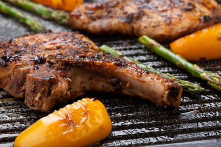 griddle: Juicy pork chops are grilled on griddle with asparagus and bell pepper  Backyard grilling for summer picnic
