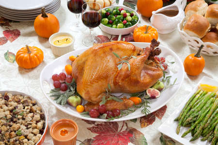 Roasted turkey on a server tray garnished with fresh figs, grape, kumquat, and herbs on fall harvest table  Red wine, side dishes, pie, and gravy  Decoraded with mini pumpkins, candels, and flowers  photo