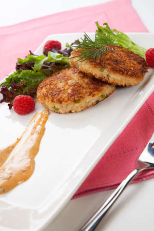 Two crab cakes appetizer garnished with spicy sauce, green salad, and raspbery  photo