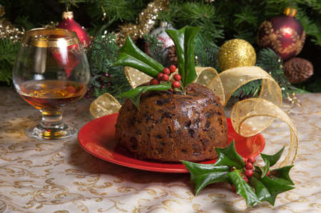 Holiday table with Christmas pudding decorated with holly twig, glass of brandy, ornaments, candles, and xmas tree  Stock Photo