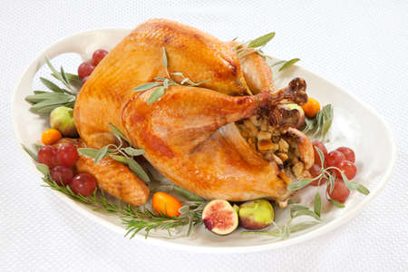 roasted turkey: Roasted turkey on tray garnished with red grapes, figs, kumquat, and herbs over white