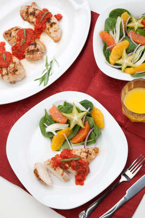 A la carte served grilled chicken breast with spinach - citrus salad served with fresh tomato tarragon sauce and orange juice