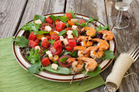 feta: Plate of a grilled shrimp salad with feta cheese, tomatoes, and watermelon in a rustic setting