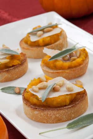 Plate full of savory butternut-sage crostini surrounded by pumpkins